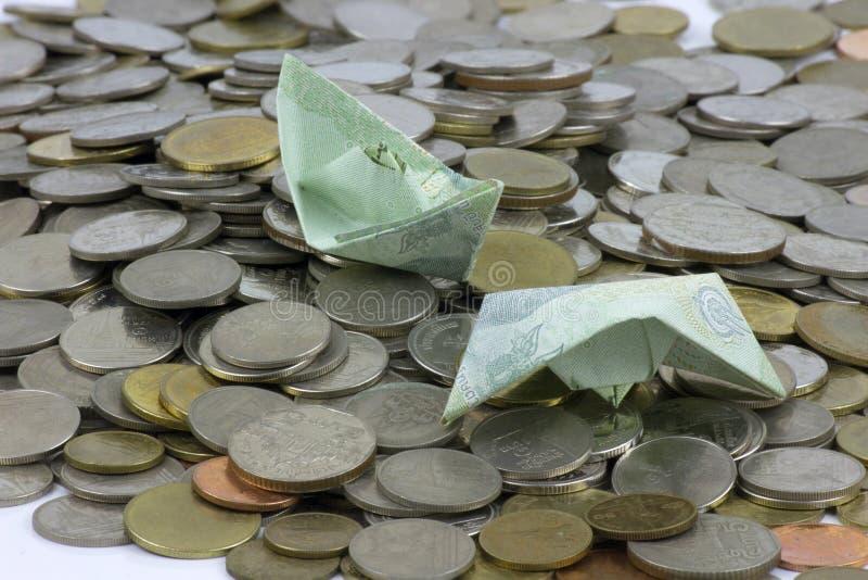 Thailand-Währungsmünzen und -rechnung gefaltet zu den Schiffen Origamikunst Geld von Thailand stockfotografie