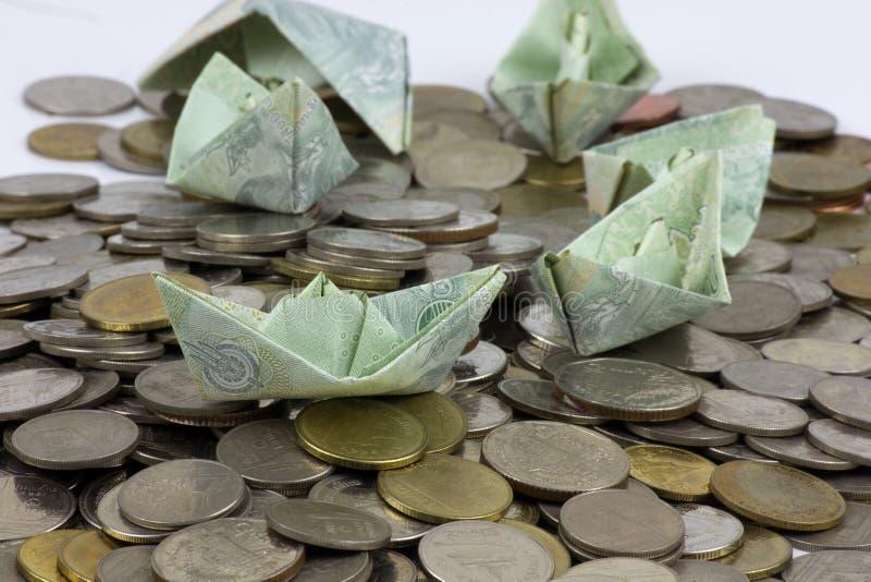 Thailand-Währungsmünzen und -rechnung gefaltet zu den Schiffen Origamikunst Geld von Thailand auf weißem Hintergrund stockfotografie