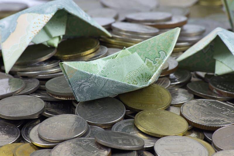 Thailand-W?hrungsm?nzen und -rechnung gefaltet zu den Schiffen Origamikunst Geld von Thailand stockbild