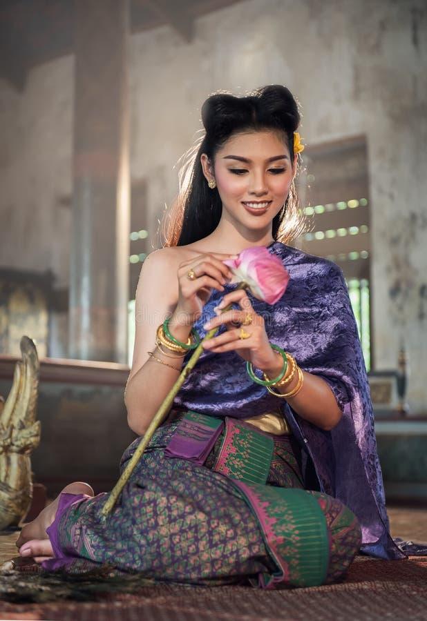 Thais meisje die lotusbloembloem in tempel maken stock foto's