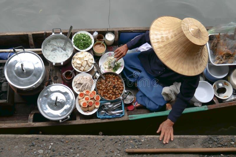 Thais voedsel in het drijven markt, verkoper met traditionele strohoed die Thais voedsel in kleine boot verkopen royalty-vrije stock foto
