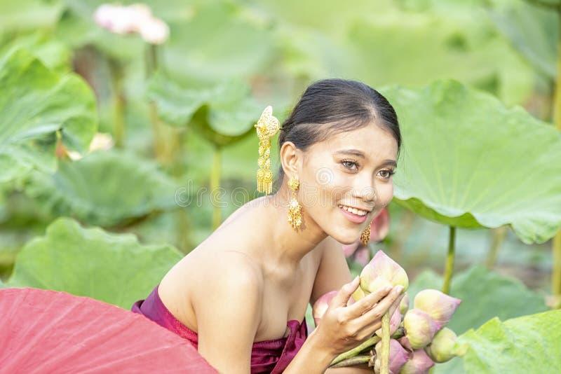 Thais wijfje op een houten boot die lotusbloembloemen verzamelen Aziatische vrouwen die op houten boten zitten om lotusbloem te v royalty-vrije stock foto's