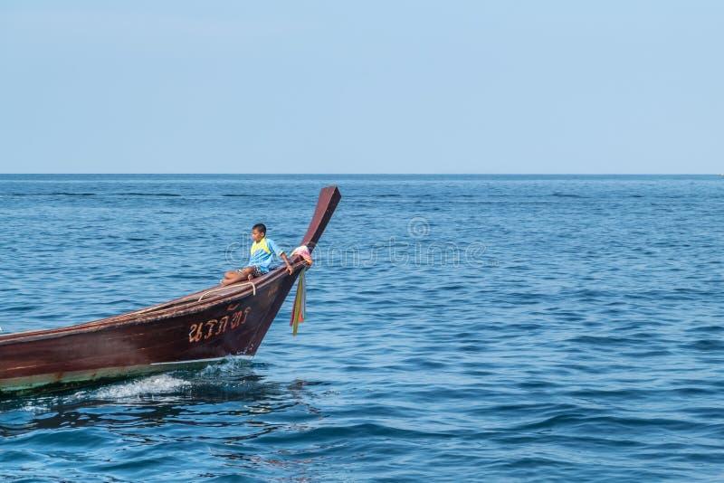 Thaise jongenszitting op hoofd van lange staartboot stock foto