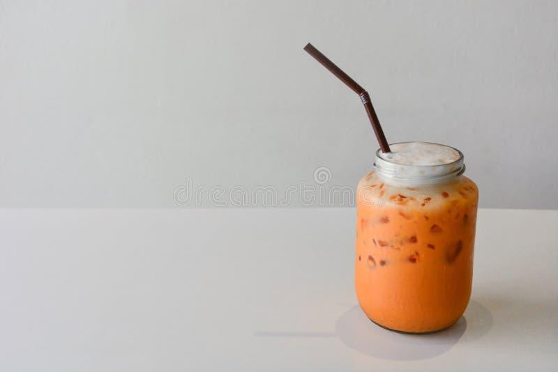 Thaise koude zoete frisdrank, glas bevroren melkthee op de lijst, witte achtergrond stock fotografie