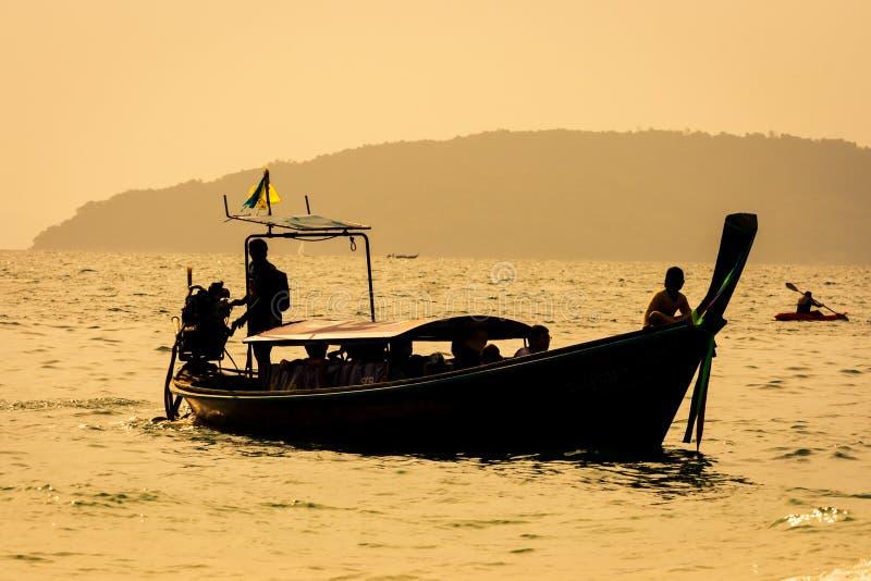 Thaise lange boot en een kajak op zee bij zonsondergang, met gouden kleuren, in Railay-strand, Krabi, Thailand stock afbeelding