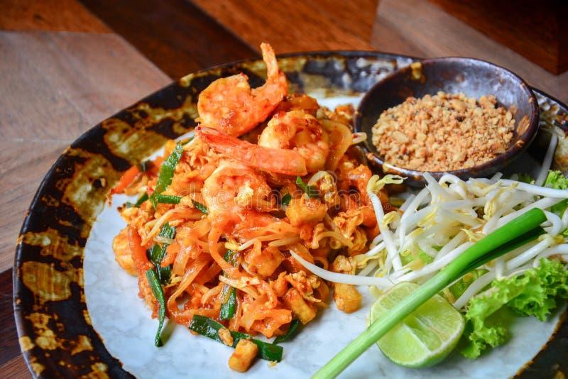 Thaise levensmiddelen, roeren van rijstnoedels met garnalen, tofu, groente en fijngemaakte pinda's of gaasjes op houten tafel royalty-vrije stock foto's