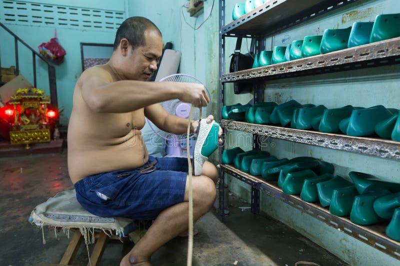 Thaise mens die in schoenenfabriek werken stock foto's