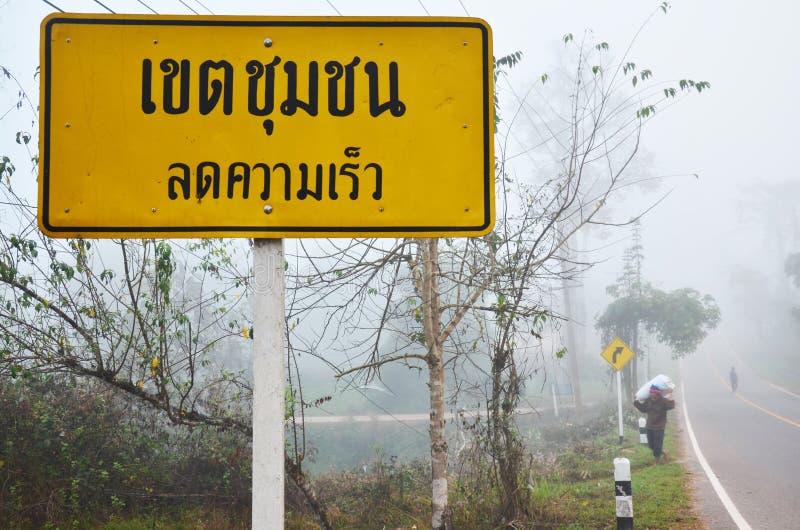 Thaise mensen die zak dragen die bij naast weg met verkeersteken lopen stock afbeeldingen