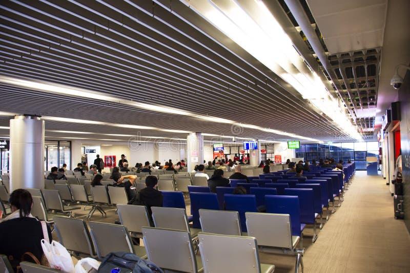 Thaise mensen en vreemdelingsreizigers die en wachtende controle in binnen van de Internationale Luchthaven van Udonthani in Thai stock foto's