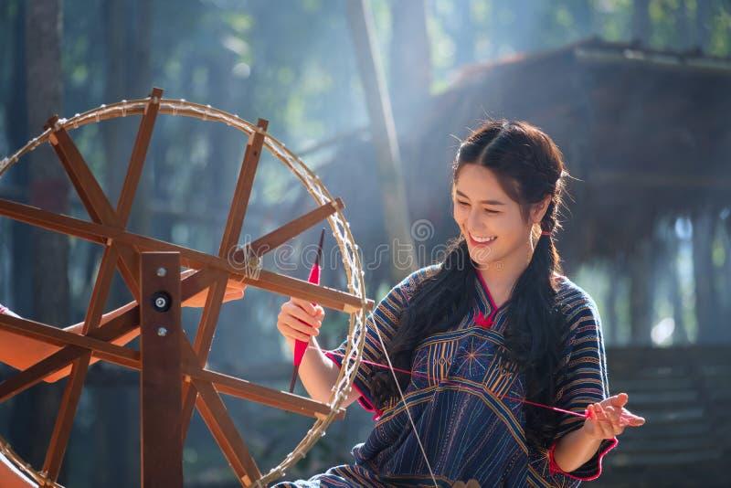 Thaise Mooie vrouwenglimlach in het kostuum spinnende draad van Karen op bedelaars stock foto's