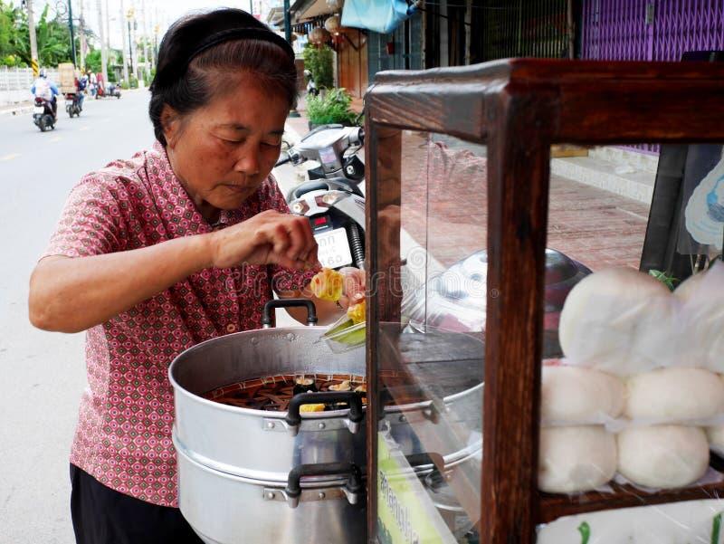 Thaise oude vrouw die gestoomde gevulde broodjes in pot voorbereiden die druk op fiets de met drie wielen van de voedselwinkel vo stock afbeeldingen