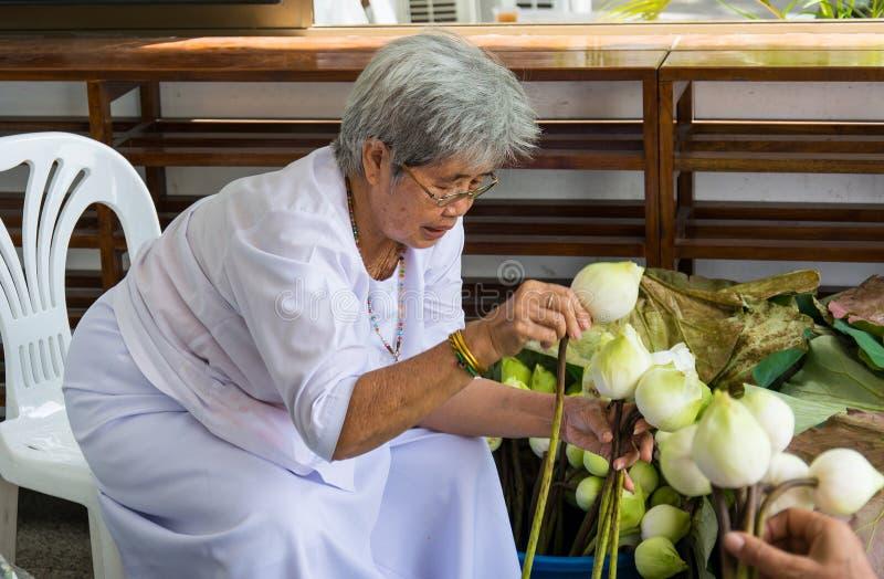 Thaise oudere vrouw die lotusbloem voor mensen voorbereiden om buddh te aanbidden royalty-vrije stock foto's