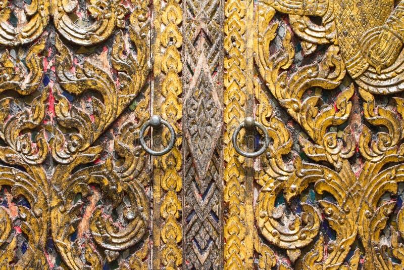 Thaise stijl houten deur met messingskloppers stock afbeeldingen