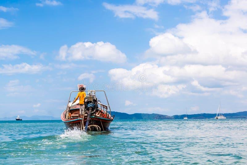 Thaise visser die in het overzees op een lang-staartboot varen Aan vissen Op de achtergrond van het jacht en de cruisevoering Kus stock foto