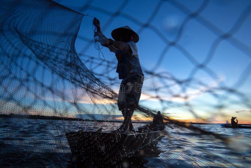Thaise visser op houten boot die een net gieten royalty-vrije stock afbeelding