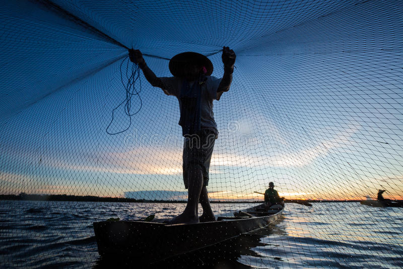 Thaise visser op houten boot die een net gieten stock afbeeldingen