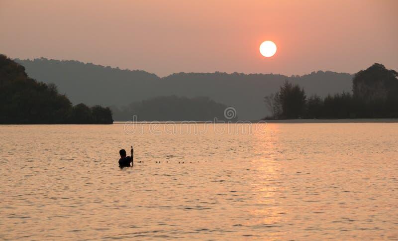 Thaise vissers plaatsende visnetten vóór eb bij zonsondergang stock foto's
