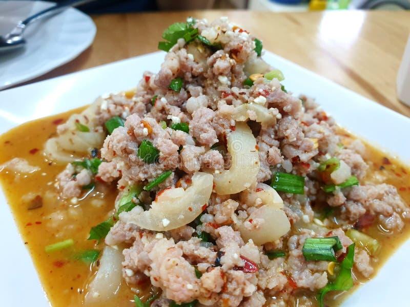 Thaise voedselstijl, Kruidige fijngehakte varkensvleessalade op witte plaat in restaurant stock foto