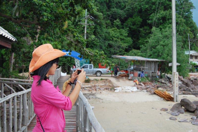 Thaise vrouw die zich op de brug bij de Visserij van Dorp Koh Phithak Island bevinden stock fotografie