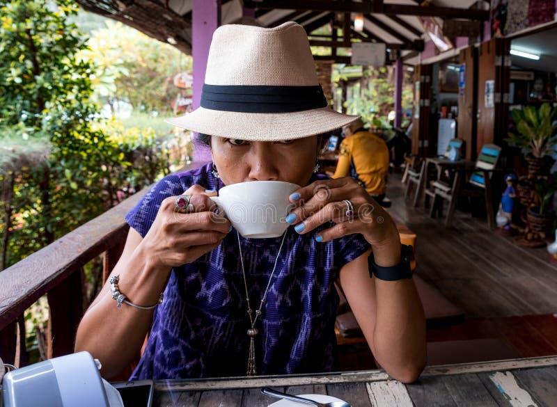 Thaise vrouw met fedora-hoed in café om koffie te drinken stock afbeelding