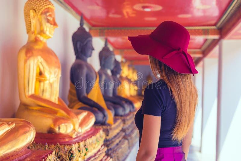 Thaise vrouwen die met hoed bekijken rijen van buddhas in Wat Pho-tempel in Bangkok, Thailand royalty-vrije stock foto's