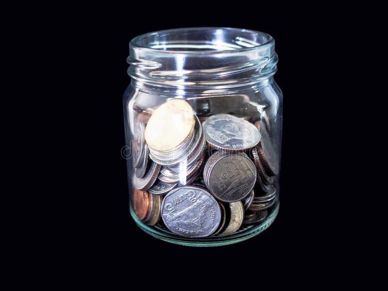 Thaise zilveren muntstukken in glasflessen die geld voor investering in de toekomst verzamelen stock afbeelding