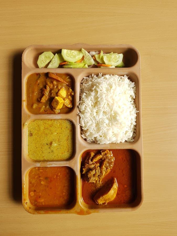 Thali indiano da galinha com caril do vegetal de salada de frango do dal do arroz em uma placa segmentada plástica no fundo de ma imagem de stock
