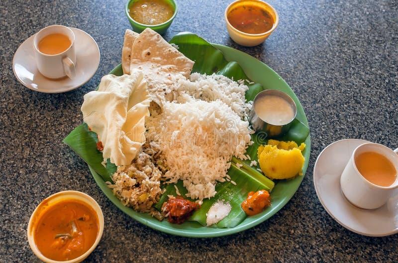 Thali indio de la comida de Vegeterian con salsa picante o salmuera, arroz, verduras picantes y dulces en hoja de palma en café i fotografía de archivo libre de regalías