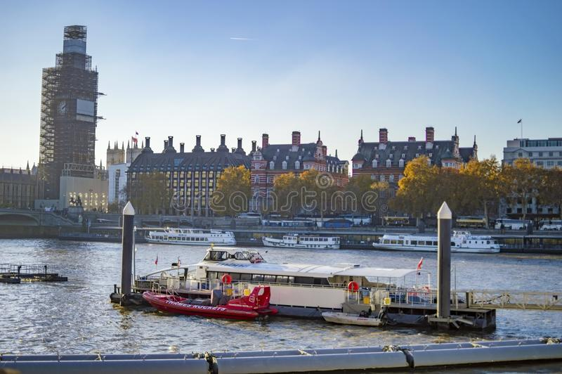 Thames river cruises and boats in the water and across the bridge big ben and parliaments are also in view stock photos
