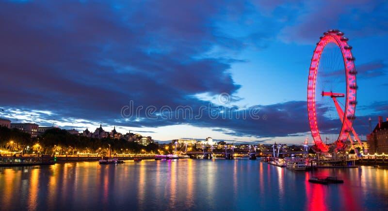 Thames River och London öga på natten royaltyfri foto