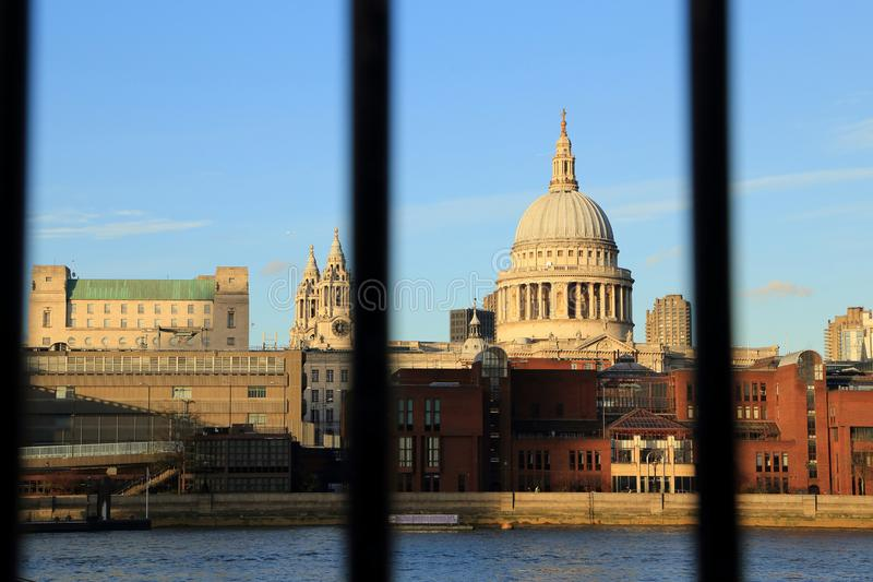 Thames river view with riverside buildings and st pauls cathedral dome look through blurred rail stock image