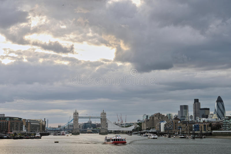 Thames with Tower Bridge London, other landmarks. Pleasure boat travelling east on the River Thames, with Tower Bridge, being refurbished for the Olympics, and stock images