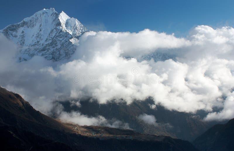 Thamserku alza, villaggio di Phortse e belle nuvole - trek al campo basso di Everest fotografie stock