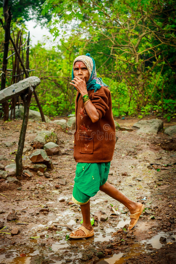 THANE, INDIA: SIERPIEŃ 6, 2016 - Stare wiosek kobiety chodzi na błotnistej drodze fotografia stock