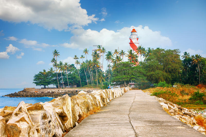 Thangassery Lighthouse on the cliff surrounded by palm trees and big sea waves on the Kollam beach. Kerala, India. Thangassery red and white stripe Lighthouse on stock photo