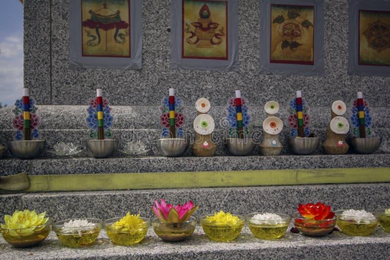 Thangka, placas del aceite esencial, flores, ofrendas en un stupa budista del granito imagen de archivo