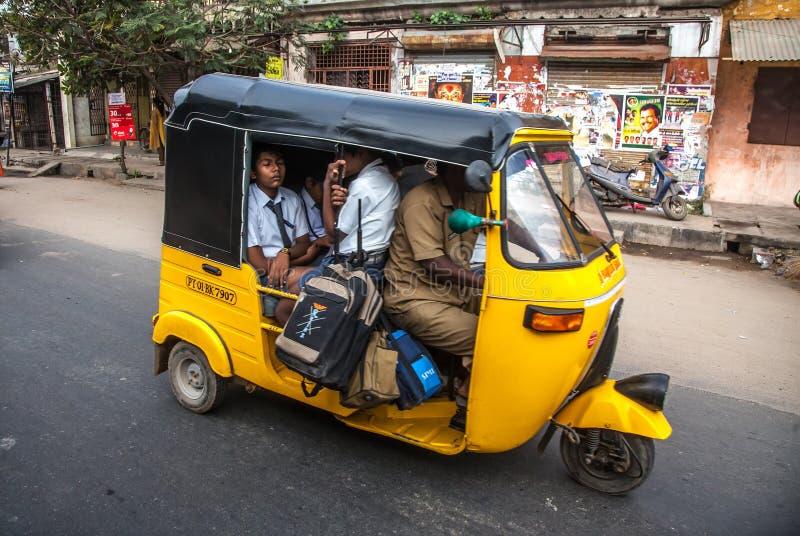 THANJAVUR, LA INDIA - 13 DE FEBRERO: Los niños van a la escuela por ri auto fotos de archivo