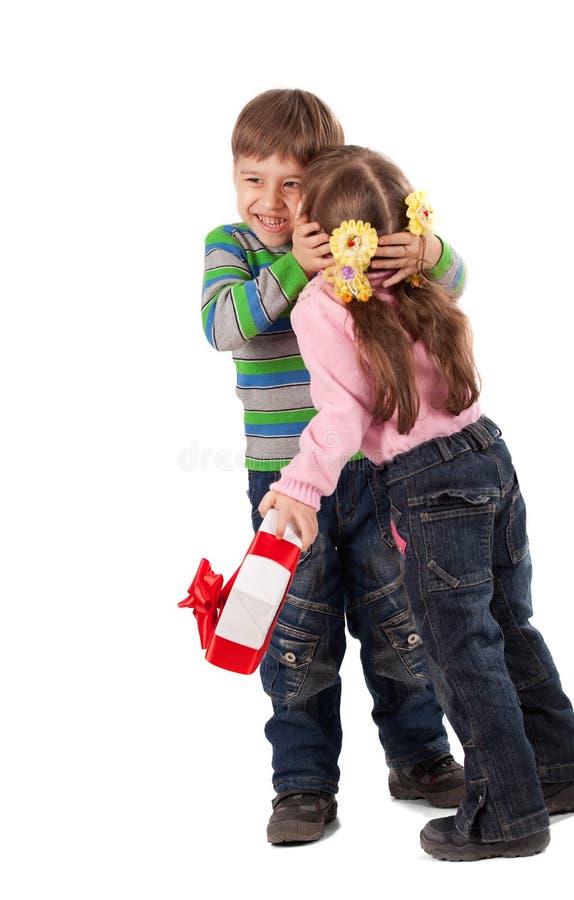 Thank you. Happy adorable little girl giving a kiss to boy, holding gift box stock photos