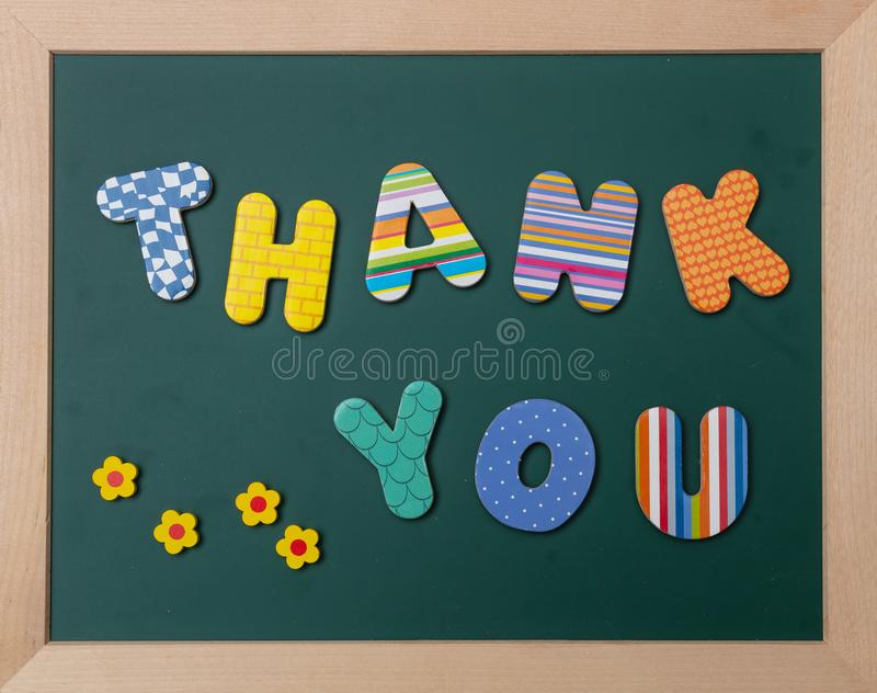 Colorful letters shaping the word thank you on green board with wooden frame royalty free stock images