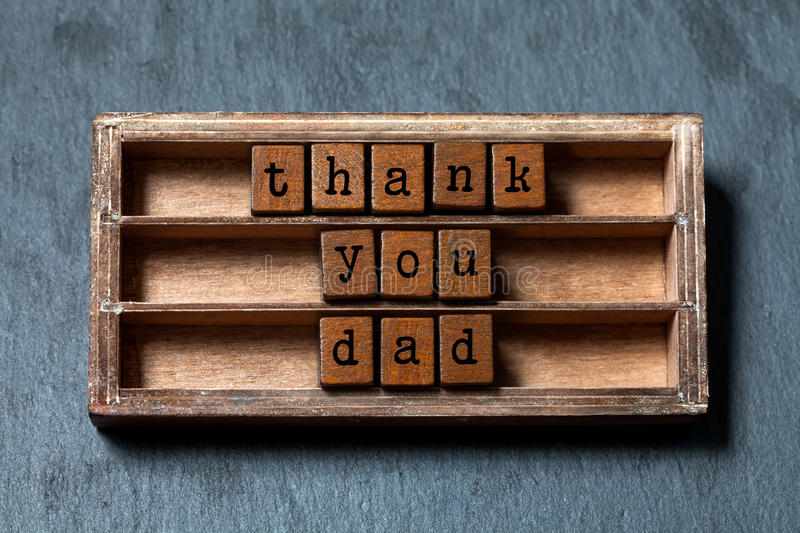 Thank you dad. Father`s day and retro greeting card. Vintage box, wooden cubes phrase with old style letters. Gray stone stock image