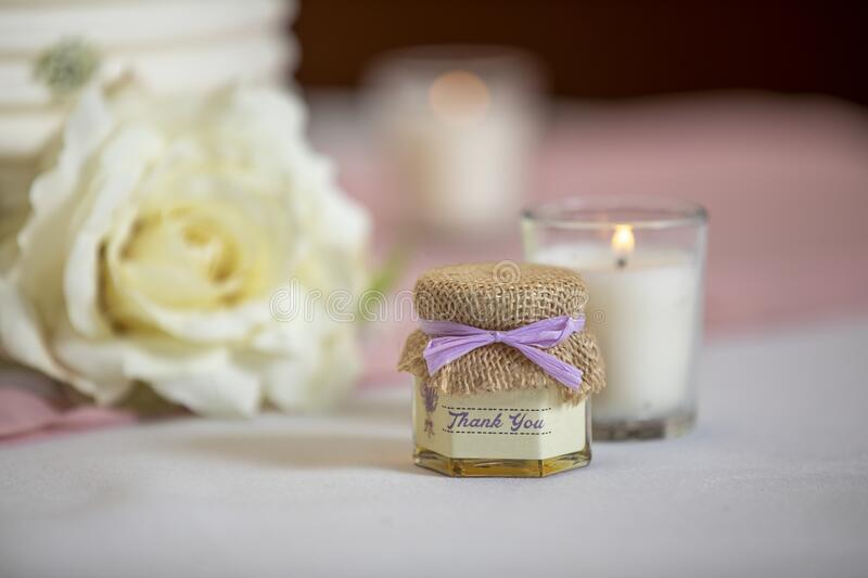 Thank you gift handout for a wedding ceremony. Handout gift and lit candle on a table at a wedding ceremony stock photos