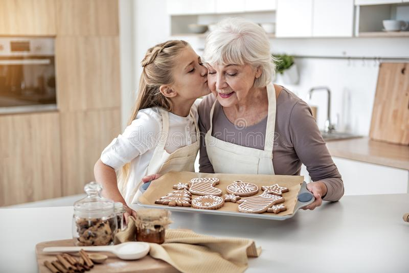Happy child thanking grandma for sweet pastry stock photography