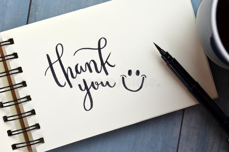 THANK YOU hand-lettered in notepad. THANK YOU hand-lettered in notebook on blue wooden desk with pen and cup of coffee stock image