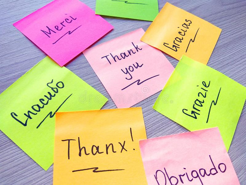 Thank you message on different languages on sticky note on wooden background stock images
