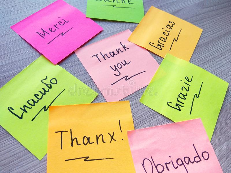 Thank you message on different languages on sticky note on wooden background stock photos