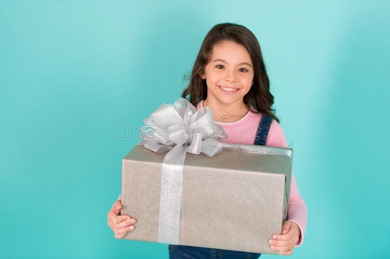 Thank you so much. Child happy face holds big gift box turquoise background. Kid girl delighted gift. Girl curly stock photo