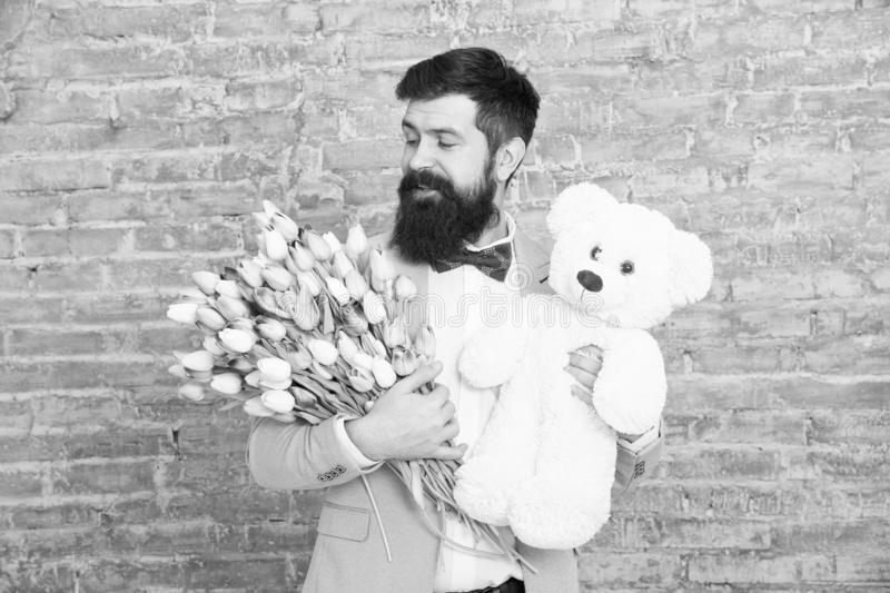 Thank you. Spring gift. Bearded man hipster with spring flowers. Bearded man with tulip bouquet and bear. Womens day. March 8. Love date. international spring royalty free stock images