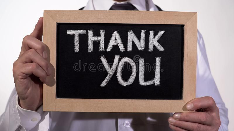 Thank you text on blackboard in therapist hands, clinic services presentation stock photography