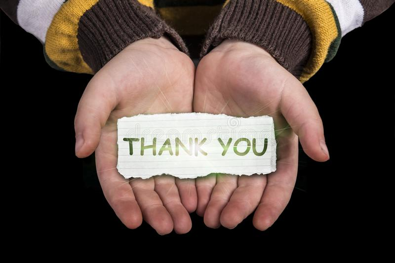 Thank you text on hand. Thank you text in line paper on child hand with glow isolated on black background royalty free stock images