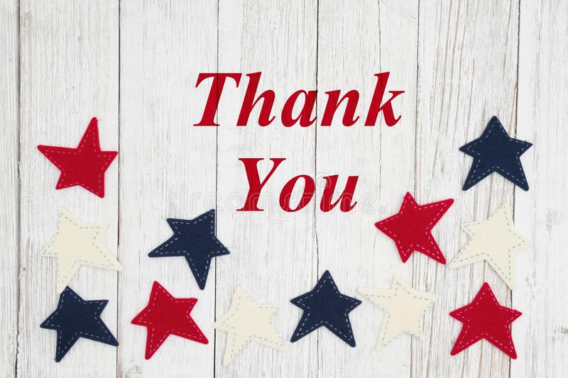 Thank you text with patriotic red, white and blue stars. On weathered whitewash textured wood royalty free illustration